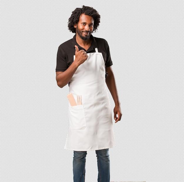 Beau boulanger afro-américain gai et excité, souriant et levant le pouce vers le haut, concept de réussite et d'approbation, geste ok