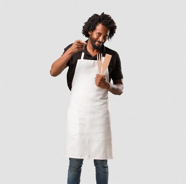 Beau boulanger afro-américain gai et souriant pointant vers l'avant