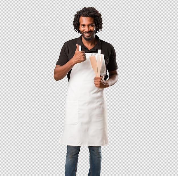 Beau boulanger afro-américain joyeux et excité, souriant et levant son pouce, concept de réussite et d'approbation, geste ok