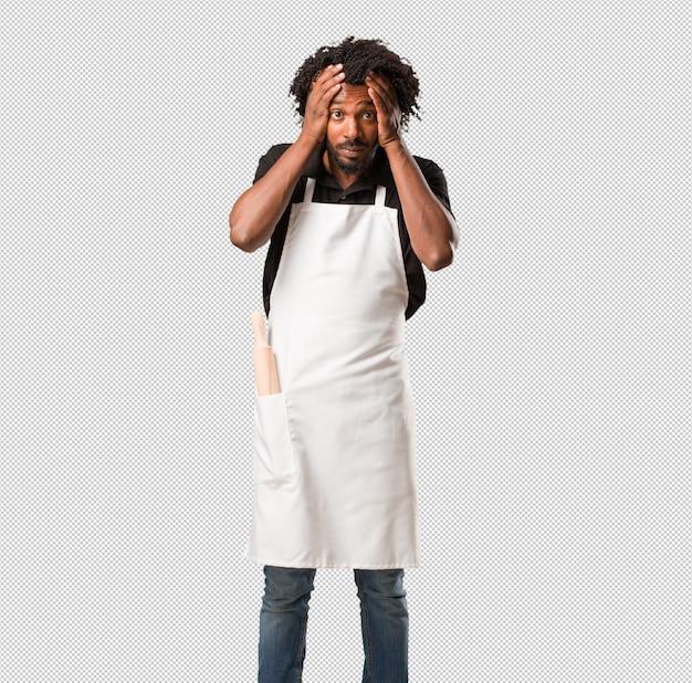 Beau boulanger homme frustré et désespéré, en colère et triste avec les mains sur la tête