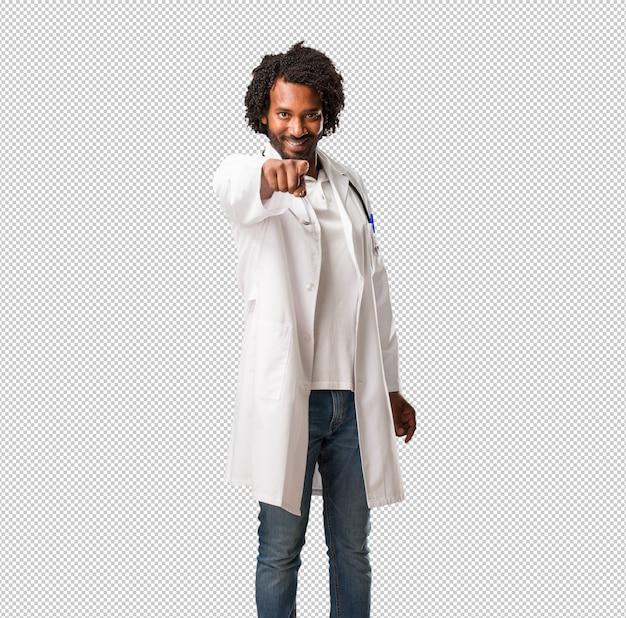 Beau docteur afro-américain gai et souriant pointant vers l'avant