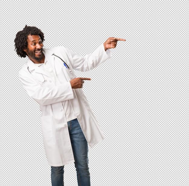 Beau docteur afro-américain pointant sur le côté