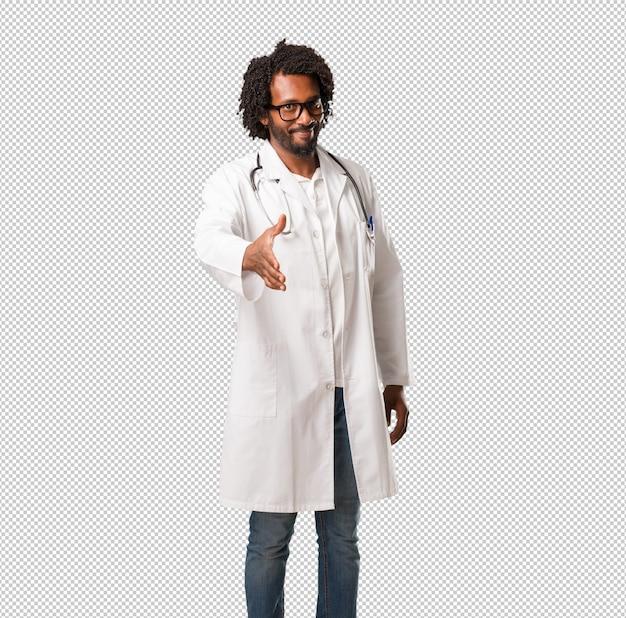 Beau docteur afro-américain tendre la main pour saluer quelqu'un ou faire des gestes pour hel