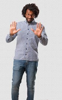 Beau homme afro-américain sérieux et déterminé, mettant la main devant, arrêter