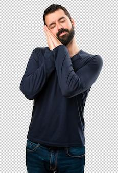 Beau homme à la barbe faisant un geste de sommeil