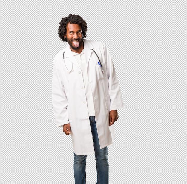 Beau médecin afro-américain expression de confiance et d'émotion, amusant et amical, montrant la langue comme signe de jeu ou de plaisir