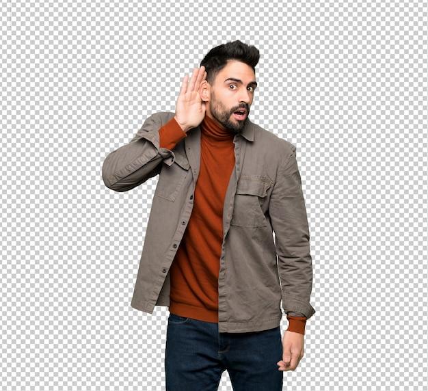 Bel homme à la barbe écoutant quelque chose en mettant la main sur l'oreille