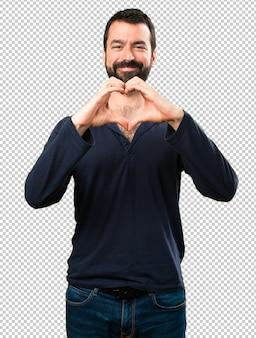 Bel homme à la barbe faisant un coeur avec ses mains