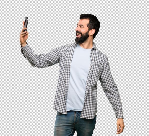 Bel homme à la barbe faisant un selfie