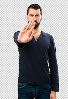 Bel homme avec barbe faisant signe d'arrêt