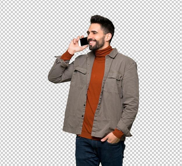 Bel homme à la barbe gardant une conversation avec le téléphone mobile