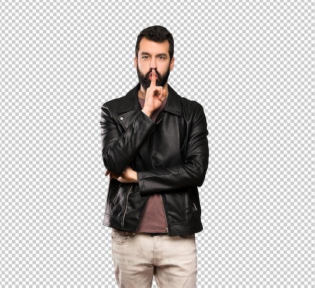 Bel homme à la barbe montrant un geste du silence mettant le doigt dans la bouche