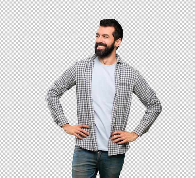 Bel homme à la barbe posant avec les bras à la hanche et souriant
