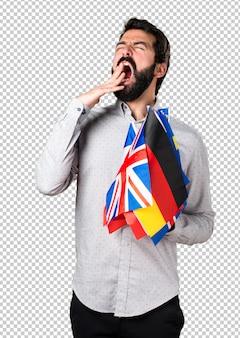 Bel homme à la barbe tenant beaucoup de drapeaux et bâillant