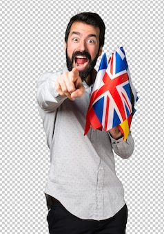 Bel homme à la barbe tenant beaucoup de drapeaux et pointant vers l'avant
