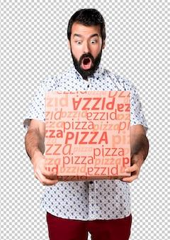 Bel homme brune à la barbe tenant une pizza