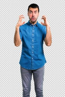 Bel homme avec une chemise bleue agacé et fâché dans un geste furieux