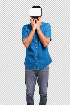 Bel homme avec une chemise bleue à l'aide de lunettes de réalité virtuelle