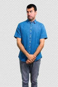 Bel homme avec une chemise bleue est un peu nerveux et effrayé