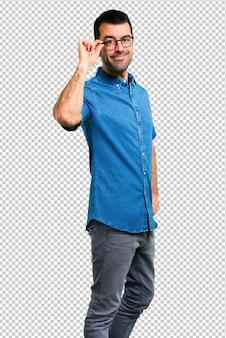 Bel homme avec une chemise bleue et des lunettes