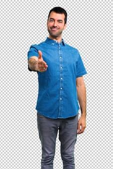 Bel homme avec chemise bleue poignée de main après bonne affaire