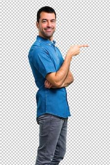 Bel homme avec une chemise bleue, pointant le doigt sur le côté et présentant un produit