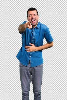 Bel homme avec une chemise bleue pointant du doigt sur quelqu'un et riant beaucoup