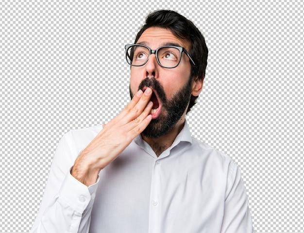 Bel homme avec des lunettes bâillant