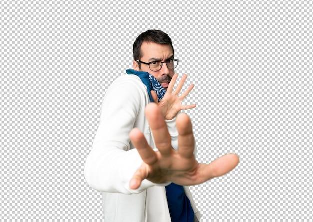 Le bel homme avec des lunettes est un peu nerveux et a peur de s'étirer les mains à l'avant