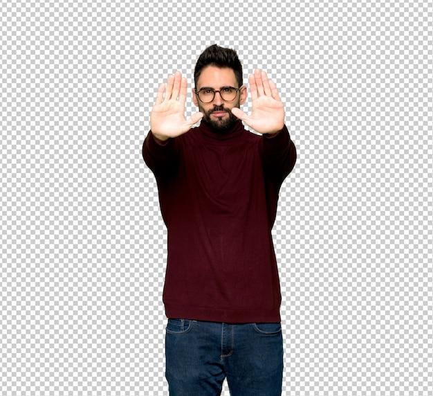 Bel homme avec des lunettes faisant arrêt geste pour déçu avec une opinion