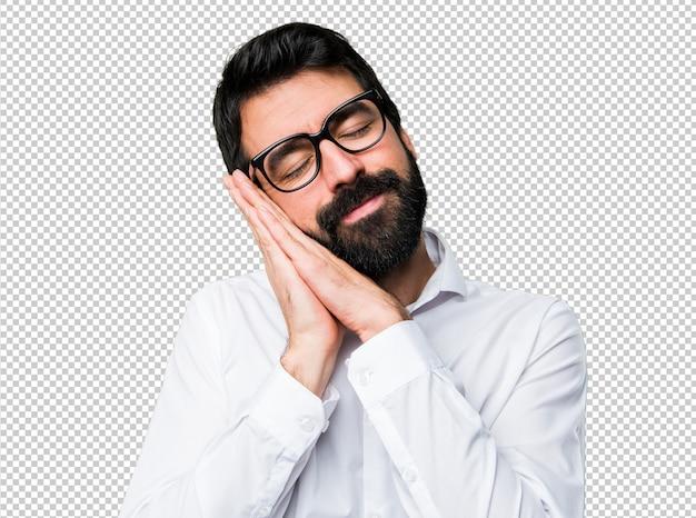 Bel homme avec des lunettes faisant un geste de sommeil