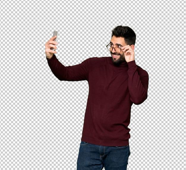 Bel homme avec des lunettes faisant un selfie