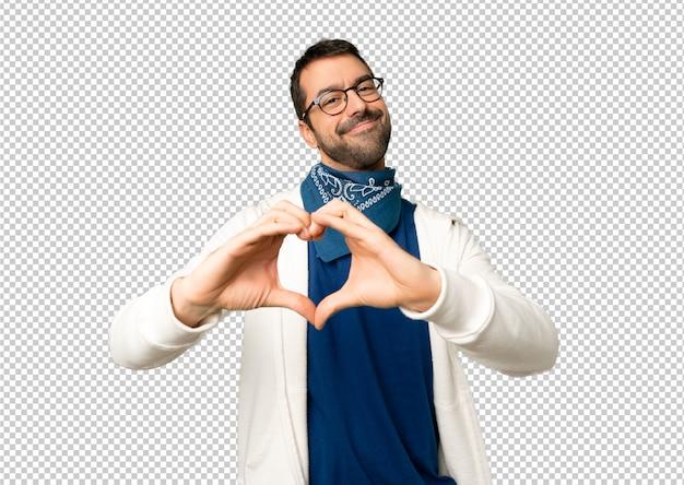 Bel homme avec des lunettes faisant le symbole du coeur par les mains