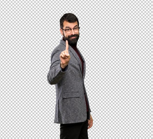 Bel homme avec des lunettes montrant et en levant un doigt