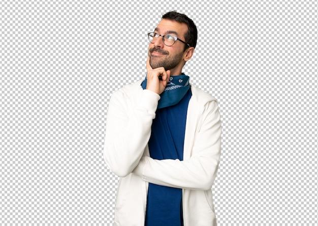 Bel homme avec des lunettes penser une idée tout en levant