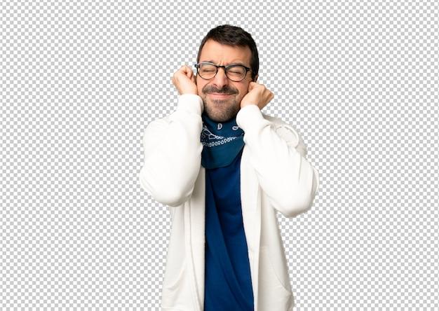 Bel homme avec des lunettes qui couvre les oreilles avec les mains. expression frustrée