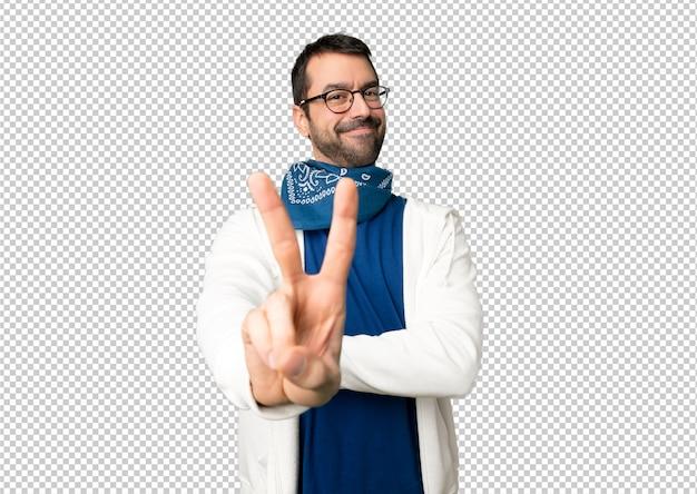 Bel homme avec des lunettes en souriant et en montrant le signe de la victoire