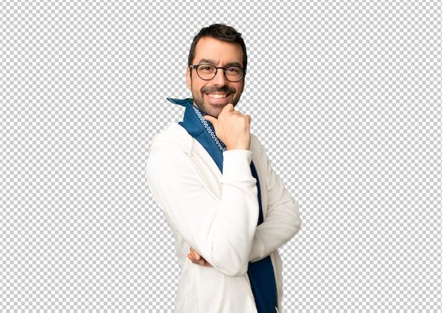 Bel homme avec des lunettes souriant et regardant vers l'avant avec un visage confiant