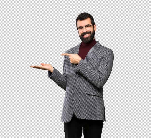Bel homme avec des lunettes tenant imaginaire copyspace sur la paume pour insérer une annonce