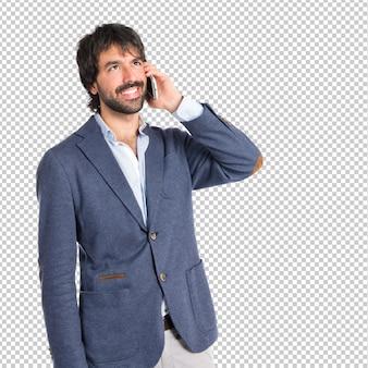 Bel homme parlant au mobile sur fond blanc