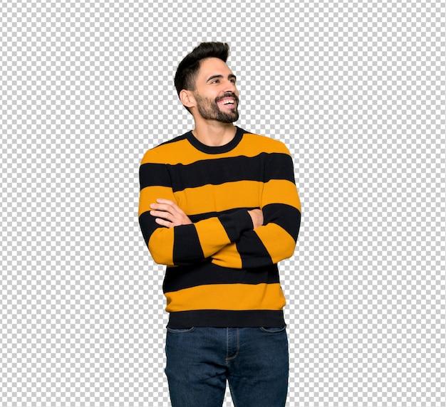 Bel homme avec pull rayé, gardant les bras croisés en souriant