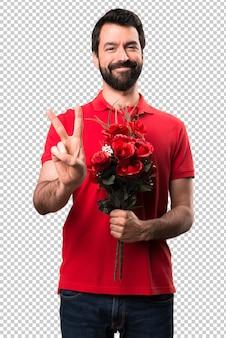 Bel homme tenant des fleurs en comptant deux