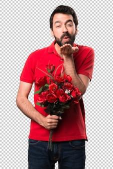 Bel homme tenant des fleurs envoie un baiser
