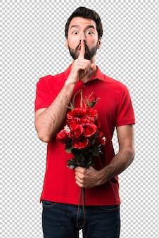 Bel homme tenant des fleurs faisant un geste de silence