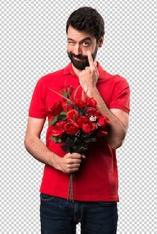 Bel homme tenant des fleurs montrant quelque chose