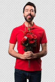 Bel homme tenant des fleurs prenant sa langue