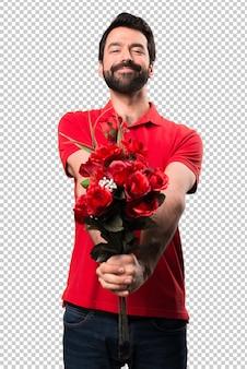 Bel homme tenant des fleurs présentant