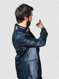 Bel homme avec veste à paillettes pointant vers l'arrière