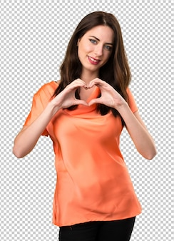 Belle jeune fille fait un coeur avec ses mains