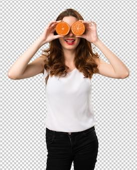 Belle jeune fille portant des tranches d'orange comme lunettes